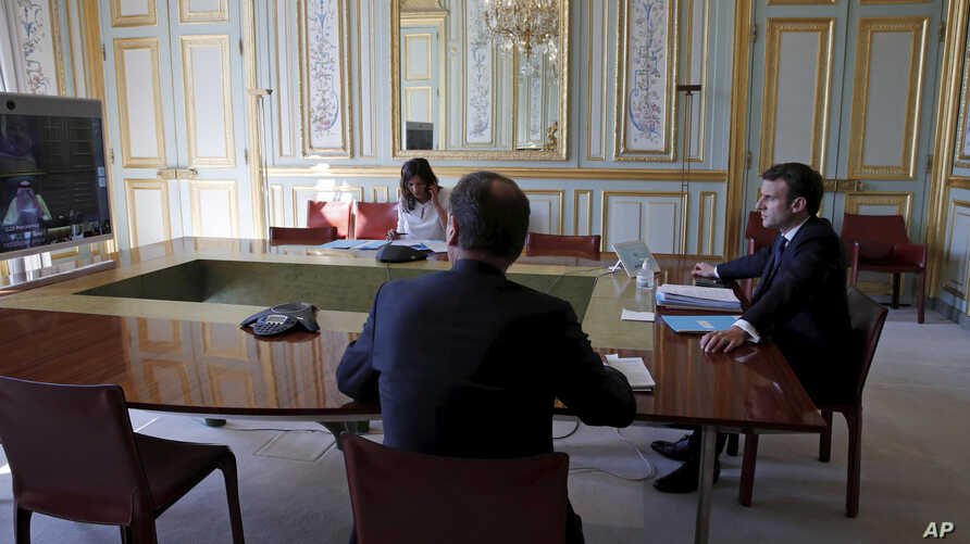 French President Emmanuel Macron, right, attends a videoconference with G20 leaders to discuss the coronavirus disease outbreak…