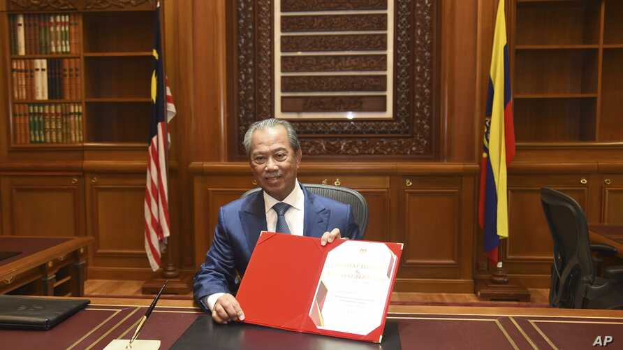 In this photo released by Malaysia's Department of Information, the country's new Prime Minister Muhyiddin Yassin poses for…