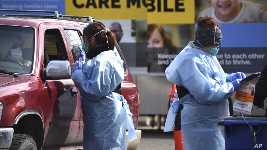 Critical care nurse Molly Spaeny, left, with St. Vincent Healthcare speaks with a patient after administering a coronavirus…