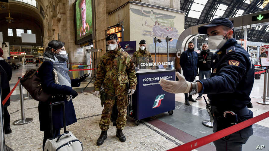 Police officers and soldiers check passengers leaving from Milan main train station, Italy, Monday, March 9, 2020. Italy took a…