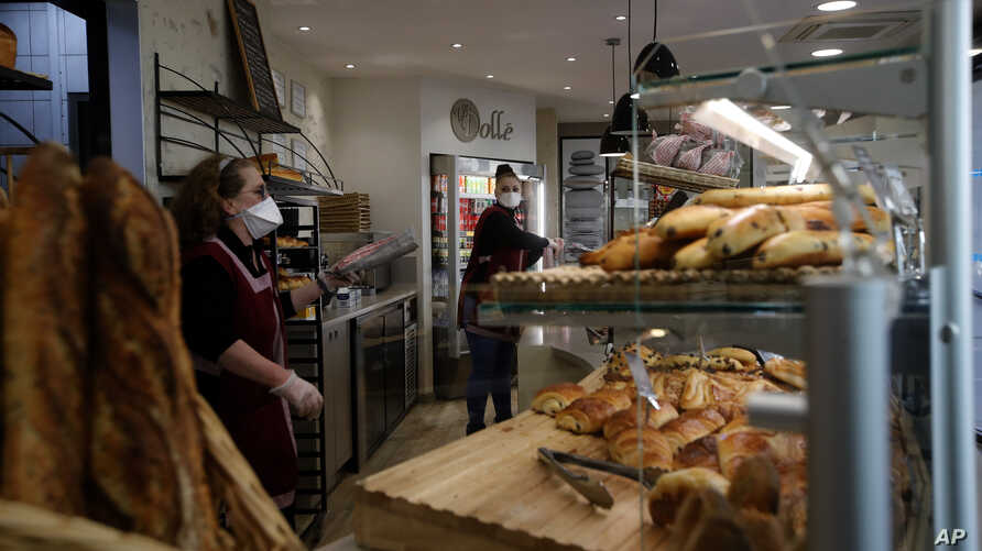 Bakers sell bread in a Boulogne Billancourt bakery, outside Paris, Tuesday, March 24, 2020. French President Emmanuel Macron…