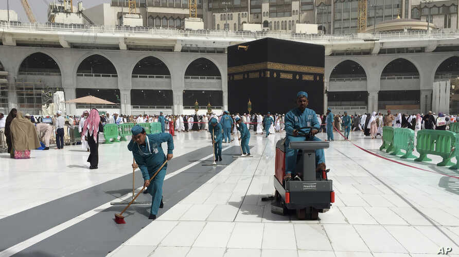 Workers clean the Grand Mosque, during the minor pilgrimage, known as Umrah, in the Muslim holy city of Mecca, Saudi Arabia,…