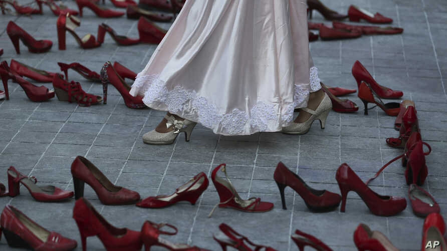 An actress walks near a line of red shoes representing murdered women, as part of a performance during the International Women…