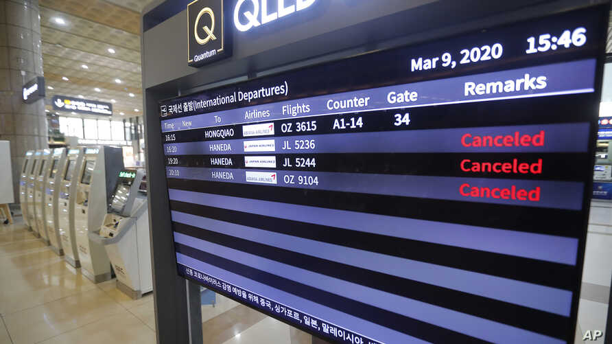 An electronic signboard shows that flights from Tokyo's Haneda airport scheduled were canceled near the self check-in system at…
