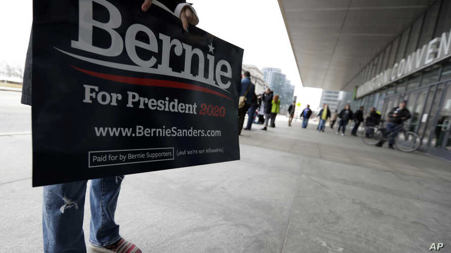 A supporter of Democratic presidential candidate Sen. Bernie Sanders, I-Vt., holds a sign outside the Huntington Convention…