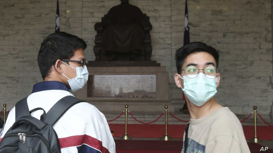 People wear face masks to protect against the spread of the new coronavirus at Chiang Kai-shek Memorial Hall in Taipei, Taiwan,…