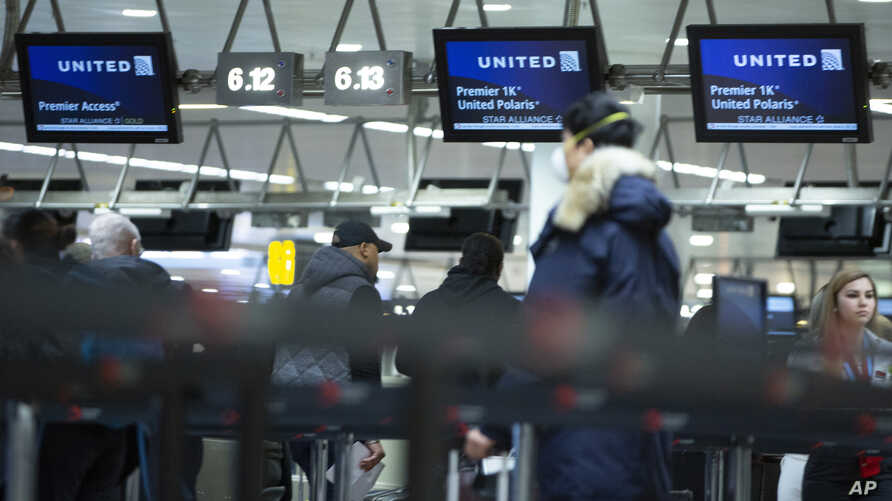 A man wears a protective mask as he waits to check into a flight to the United States in the main terminal of Brussels…