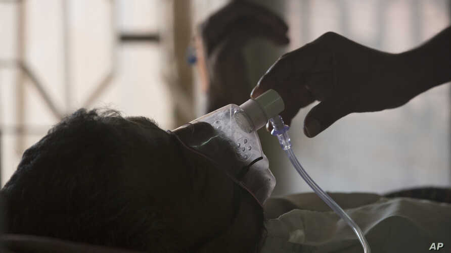A relative adjusts the oxygen mask of a tuberculosis patient at a TB hospital on World Tuberculosis Day in Hyderabad, India,…