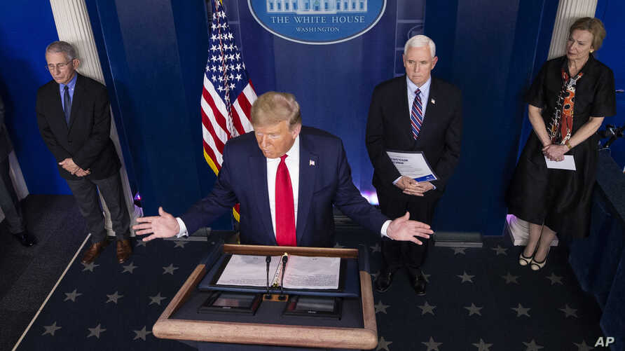 President Donald Trump speaks about the coronavirus accompanied by Dr. Anthony Fauci, left, director of the National Institute…