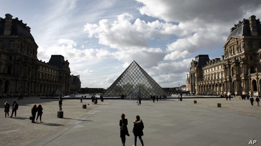 People walk by the Louvre Museum, in Paris, Friday, March 13, 2020. The Louvre Museum in Paris and the Versailles Palace both…