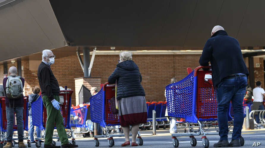 People queue at a Carrefour supermarket, waiting to enter Saturday, March 21, 2020, in Turin, Italy. Italian Premier Giuseppe…