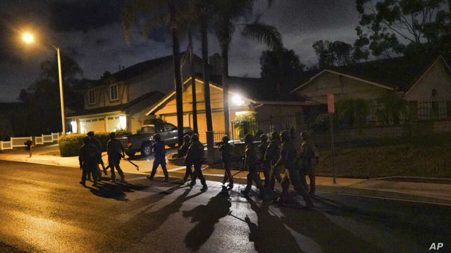 DEA agents move in on a residential house during an arrest of a suspected drug trafficker on Wednesday, March 11, 2020 in…