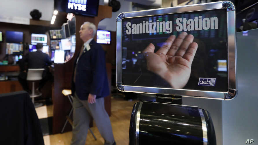 A trader passes a hand sanitizing station on the floor of the New York Stock Exchange, Tuesday, March 3, 2020. Federal Reserve…
