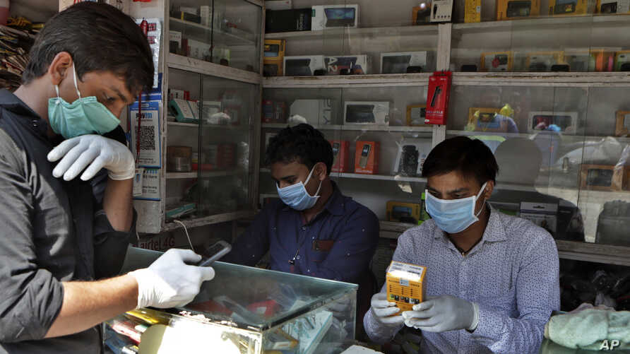 Indian mobile vendors wear protective masks and gloves as a precaution against a new virus at their outlet in Mumbai, India,…