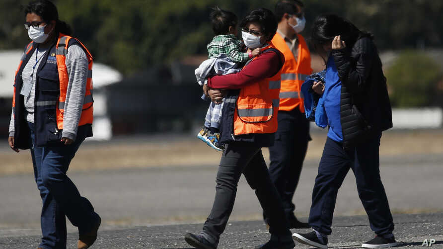 FILE - In this March 12, 2020 file photo, an immigration worker in an orange jacket and wearing a mask as a precaution against…