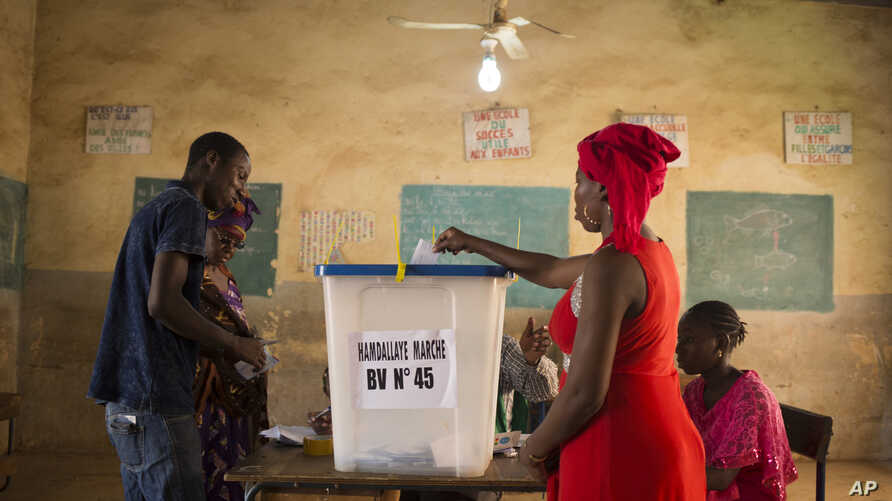 A woman casts her ballot during the Presidential second round election in Bamako Mali, Sunday, Aug 12, 2018. Malians are voting…