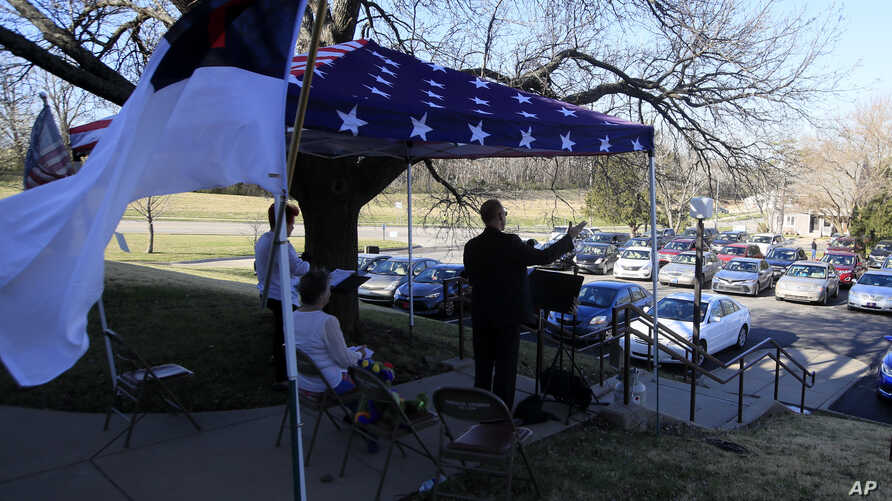 Pastor Lee leads a parking lot service at the Immanuel Lutheran Church In Lawrence, Kan., Sunday, March 29, 2020. The church…