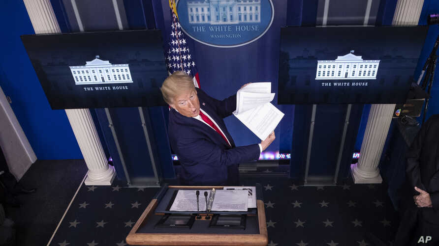 President Donald Trump flips through a stack of papers as he speaks about the coronavirus in the James Brady Press Briefing…