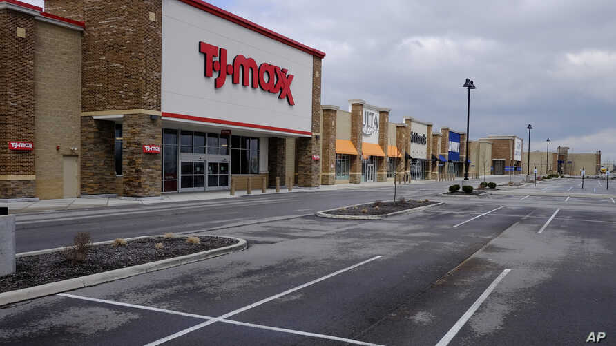 An empty parking lot is seen at retail stores are closed, Wednesday, April 15, 2020, in Whitestown, Ind. Evidence of the…