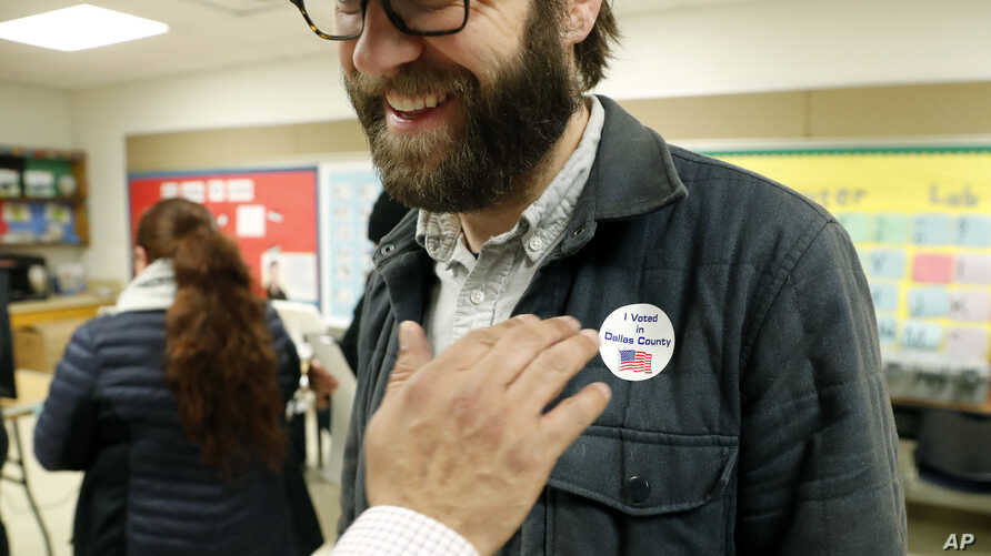 FILE - In this March 3, 2020 file photo, Democrat Jamie Wilson gets a sticker after voting in the Super Tuesday primary at John…