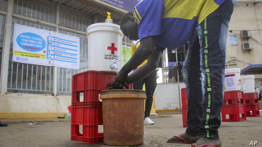 FILE - In this Monday, April 6, 2020 file photo, a man washes his hands to curb the spread of the new coronavirus in Juba,…
