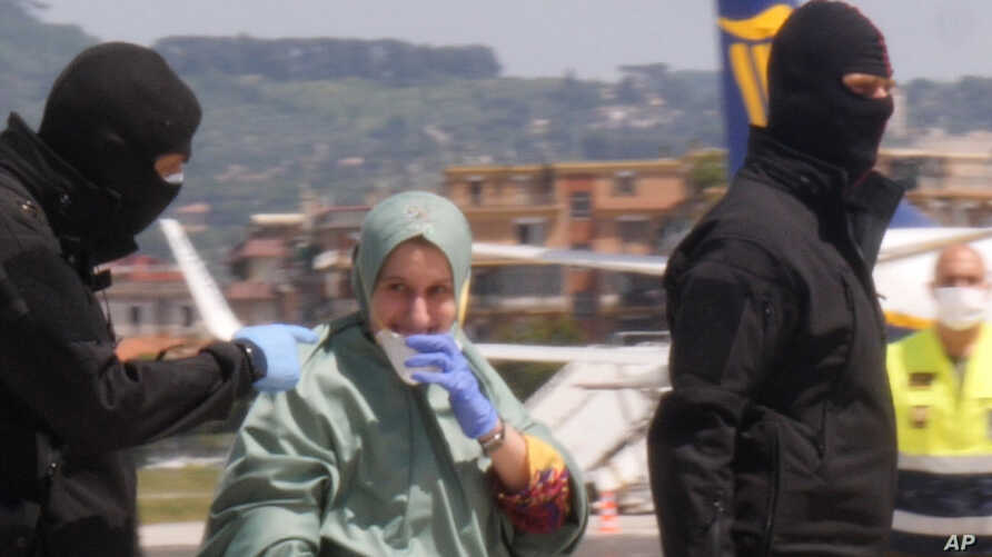 In this image taken from a video, Silvia Romano is flanked by two masked security officers as she walks on the tarmac after…
