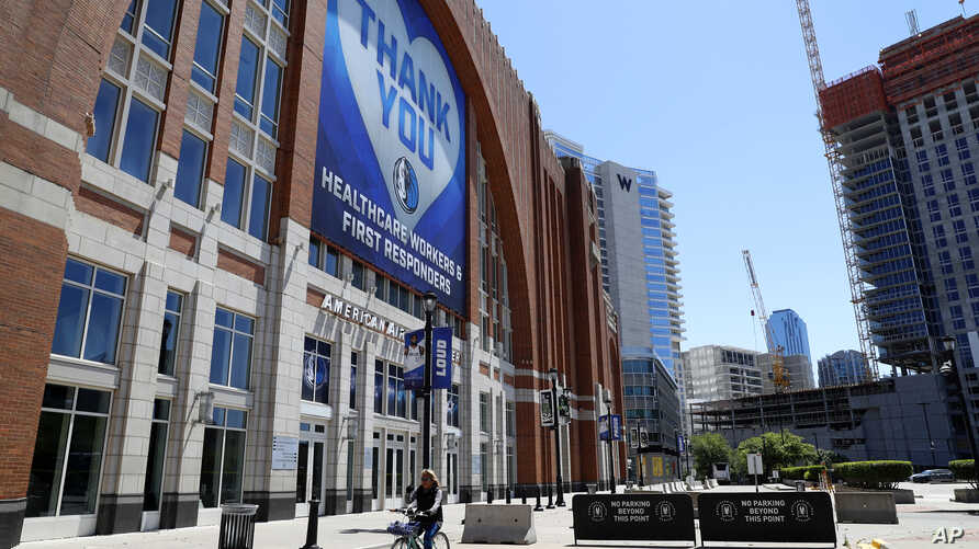 A person on a bike rides past a large banner hanging outside American Airlines Center, home of the Dallas Mavericks and the…