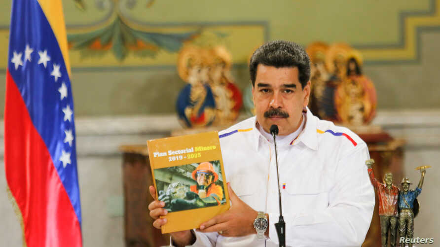 Venezuela's President Nicolas Maduro holds a book titled 'Mining Sectoral Plan' while delivering a speech during a launching of a National Mining Plan at the Miraflores palace in Caracas