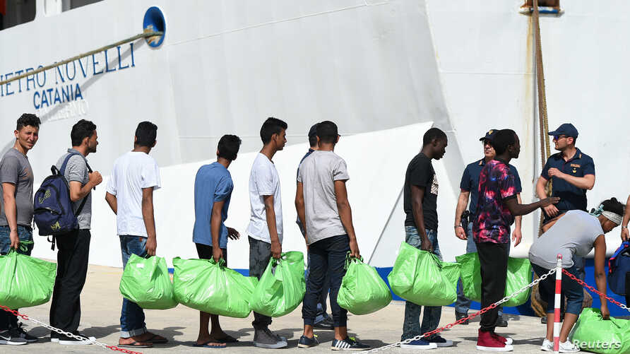 Migrants board a ferry to be transferred to mainland from the Sicilian island of Lampedusa