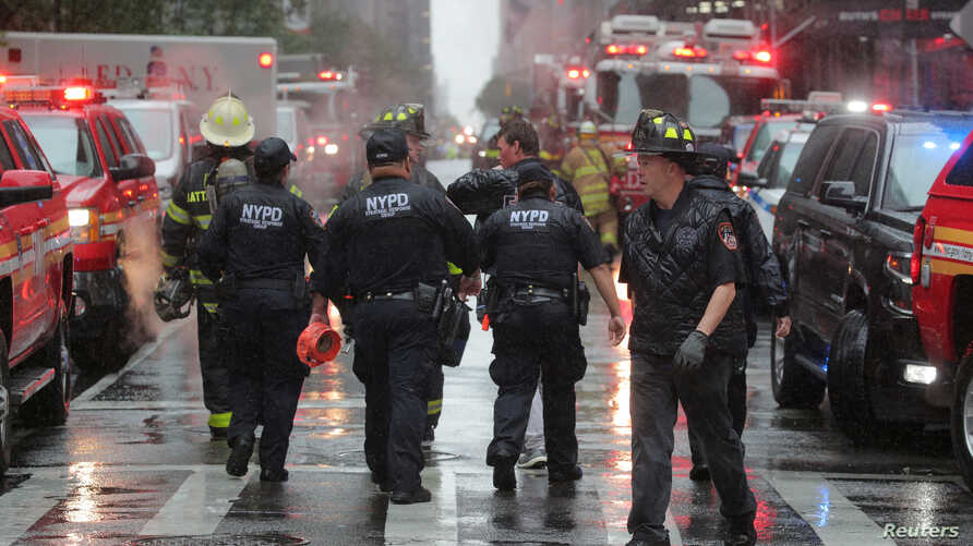 New York City police and firefighters arrive at the scene after a helicopter crashed atop a building in New York