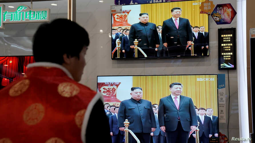 FILE - Television screens show Chinese state media CCTV's footage of North Korean leader Kim Jong Un's meeting with Chinese President Xi Jinping, in Beijing, Jan. 10, 2019.