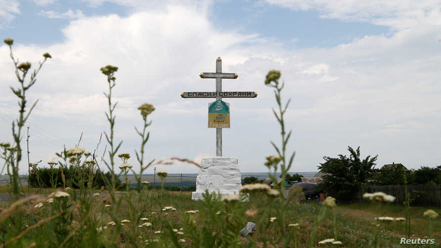 A photo shows a cross near the crash site of Malaysia Airlines Flight MH17 plane outside Hrabove.