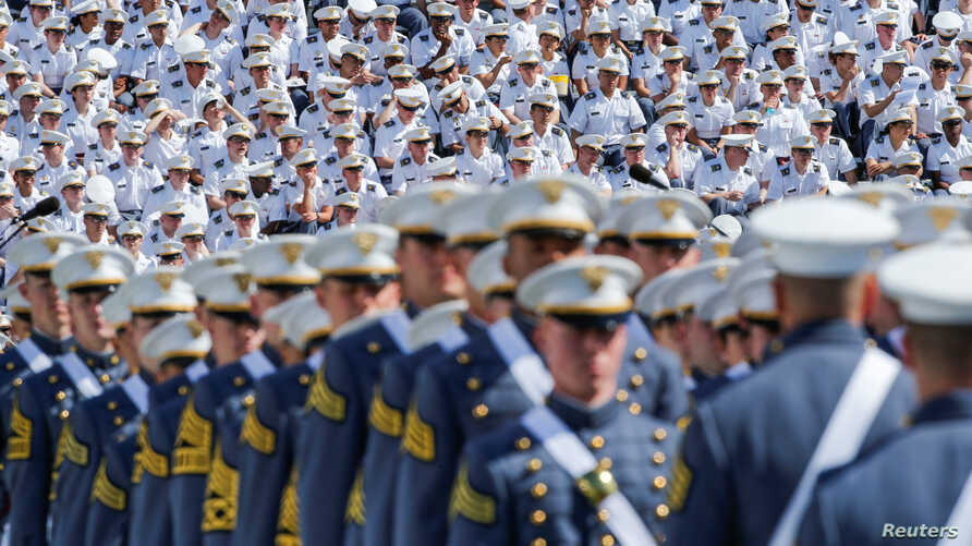Military members watch graduating Cadets as they march together for a commencement ceremony at the United States Military Academy in West Point, New York