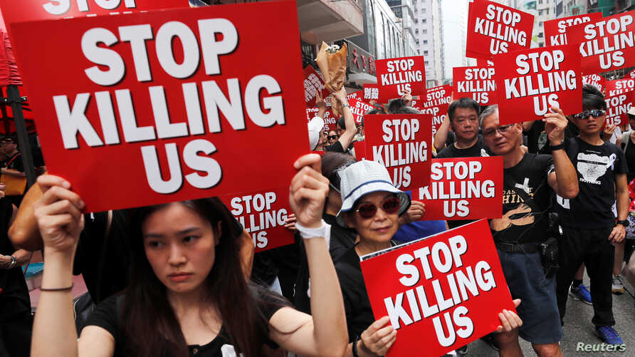 Protesters hold placards as they attend a demonstration demanding Hong Kong's leaders to step down and withdraw the extradition bill, in Hong Kong, June 16, 2019.