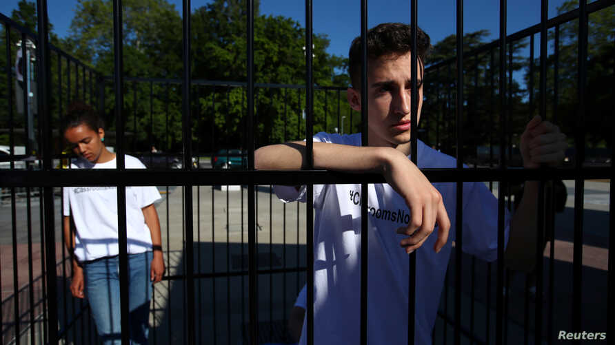 Teenagers are pictured in a cage during a demonstration to condemn the US President Trump administrationÕs policy of child detention in Geneva