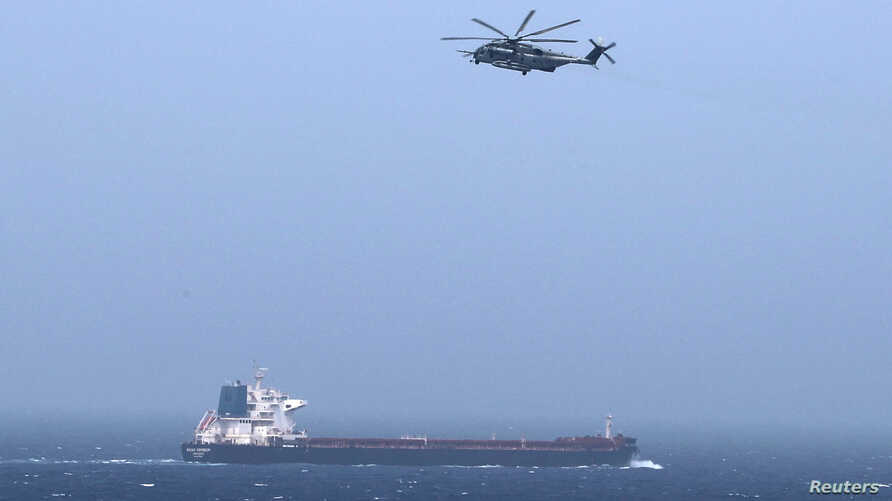 A U.S CH-53E Super Stallion aircraft flies over a tanker in the Arabian Sea off Oman