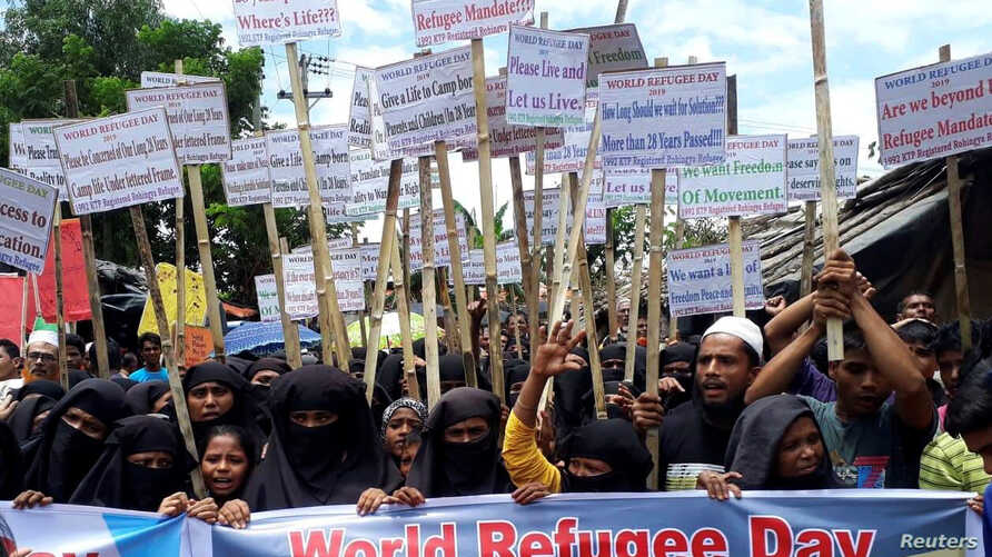 Rohingya refugees hold placards as they participate in a rally to observe World Refugee Day at the Rohingya refugee camp in Cox's Bazar, June 20, 2019.