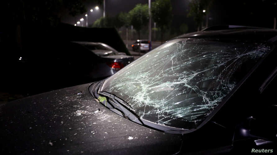 Car with damaged windshield is seen following an explosion at a Yima gas factory nearby, in Sanmenxia