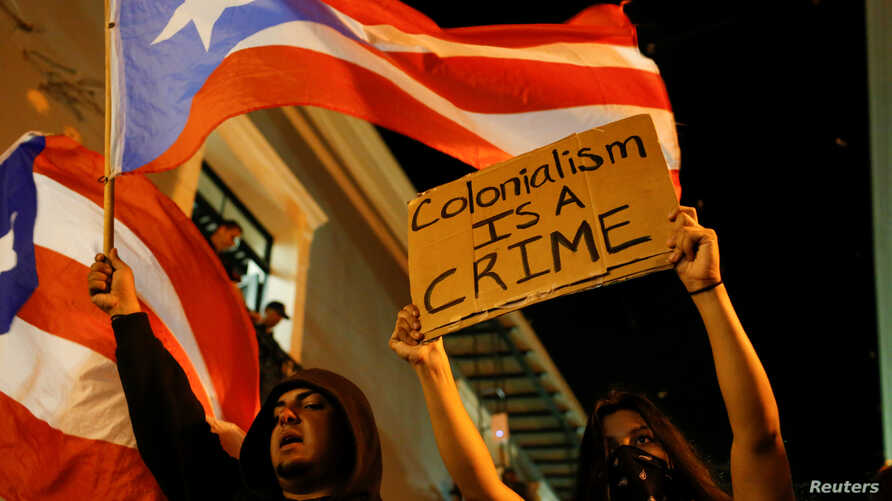 A man waves a Puerto Rican flag next to a woman that holds a sign during ongoing protests calling for the resignation of Governor Ricardo Rossello in San Juan