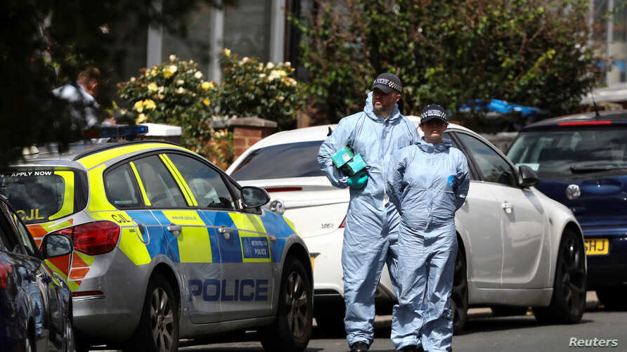 Forensic officers check for evidence in the street where a heavily pregnant woman was stabbed to death in the Thorntopn Heath area of London