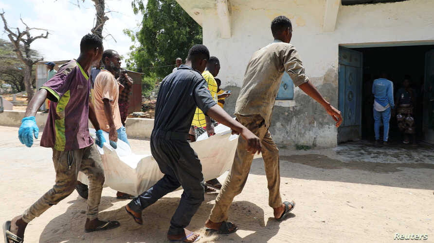 Relatives carry the dead body of a civilian killed in an explosion outside a hotel near the international airport in Mogadishu