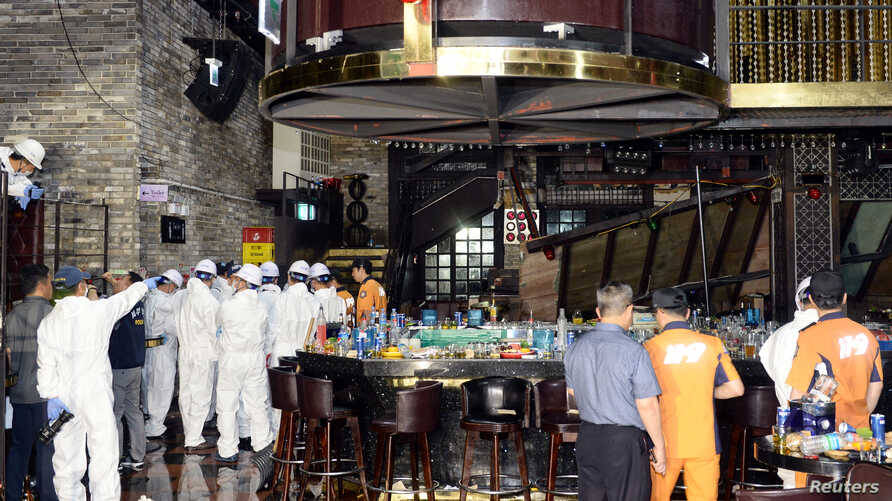 South Korean firefighters and officials examine the collapsed structure of a nightclub where several athletes competing at the World Aquatics Championships were dancing, in Gwangju, South Korea, July 27, 2019.