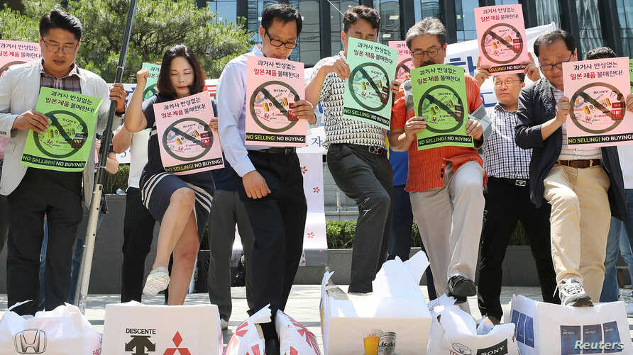 South Korean merchants step on boxes bearing logos of Japanese products during a rally to declare a boycott of Japanese goods in Seoul, South Korea, July 5, 2019.