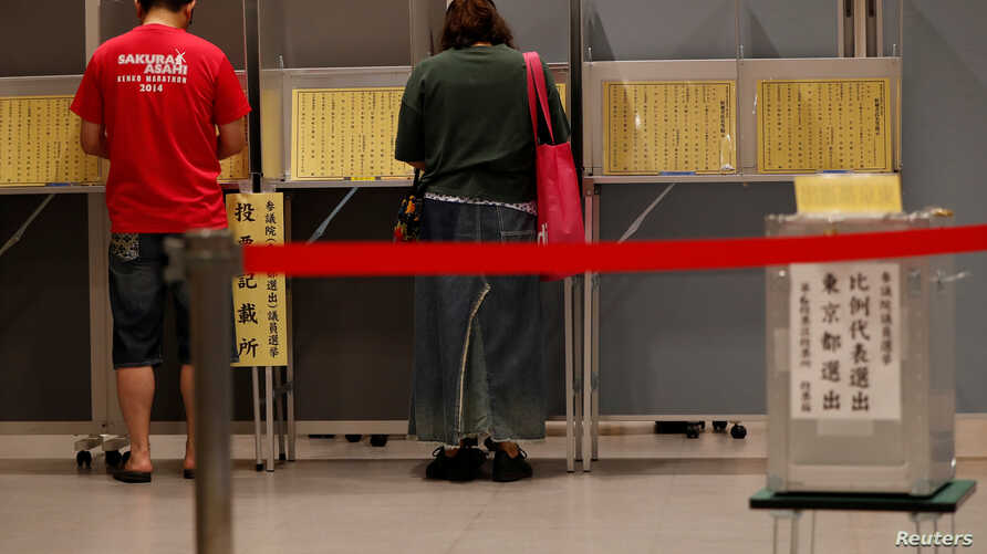 Voters fill out their ballots for Japan's upper house election at a polling station in Tokyo