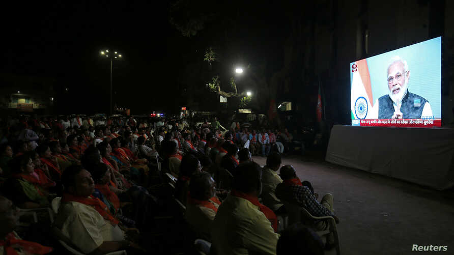 People watch as Prime Minister Narendra Modi delivers an address to the nation, on a TV screen in Ahmedabad