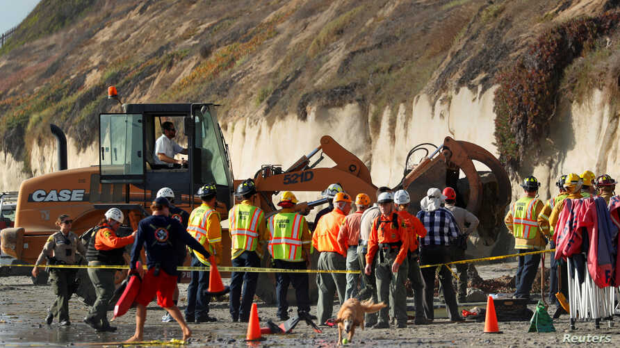 Emergency responders attend to a cliff collapse at a beach in Encinitas, California