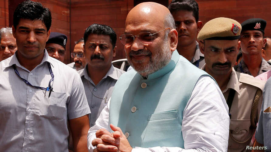FILE - India's newly appointed Home Minister Amit Shah greets the media upon his arrival at the home ministry in New Delhi, India, June 1, 2019.
