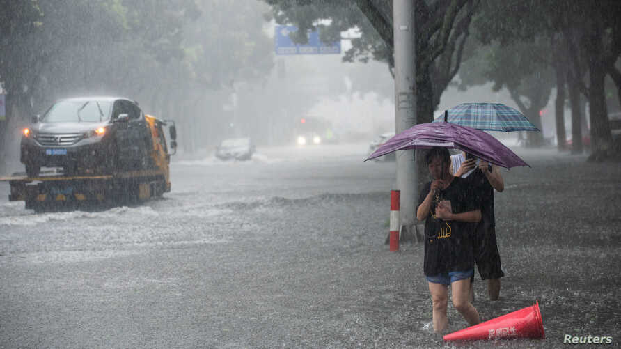 People holding umbrellas wade through floodwaters amid heavy rainfall on a street after Typhoon Lekima made landfall in Ningbo, Zhejiang province, China, Aug. 10, 2019.