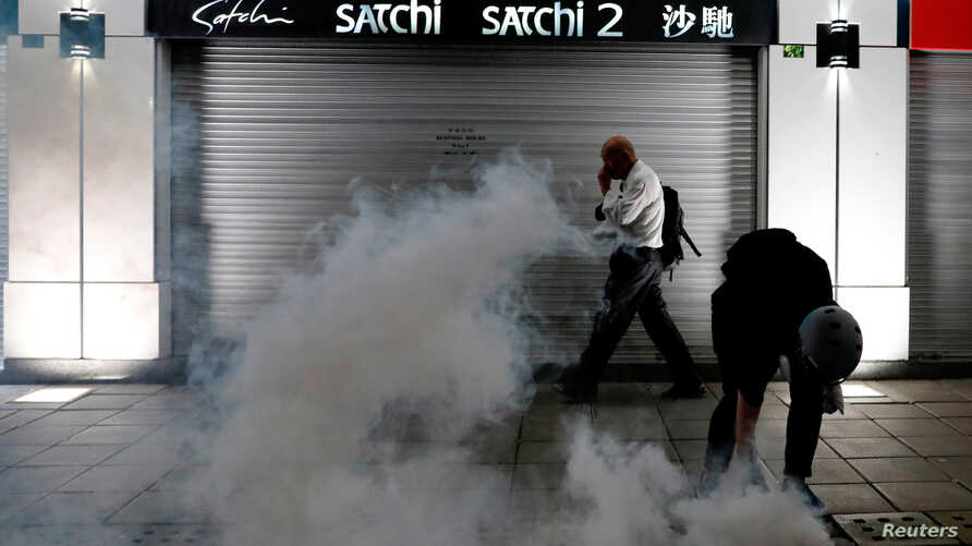 A man walks past an anti-extradition bill protester as he tries to pick up a tear gas canister at Tsim Sha Tsui after a demonstration in Hong Kong, Aug. 10, 2019
