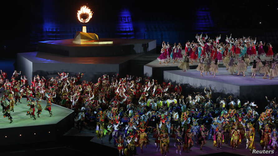 XVIII Pan American Games - Lima 2019 - Closing Ceremony- Estadio Nacional, Lima, Peru - August 11, 2019. Performers in front of the Pan Am Games flame during the closing ceremony. REUTERS/Ivan Alvarado